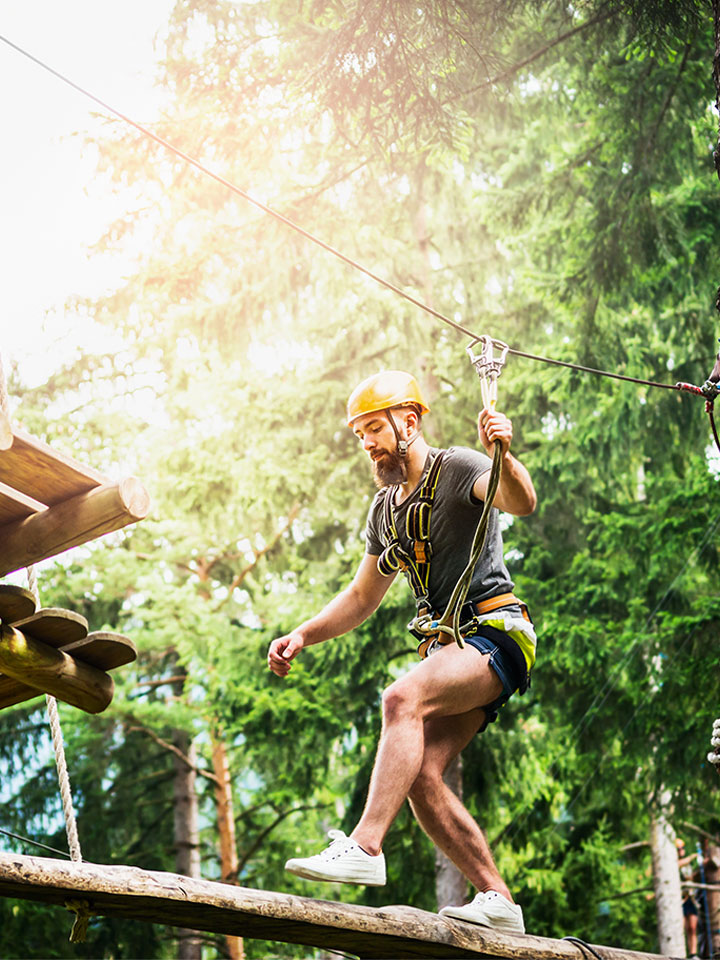 Man moving through a ropes course between trees