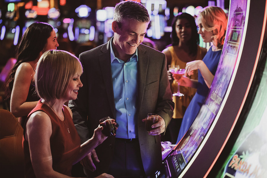 A couple playing on the casino slots.