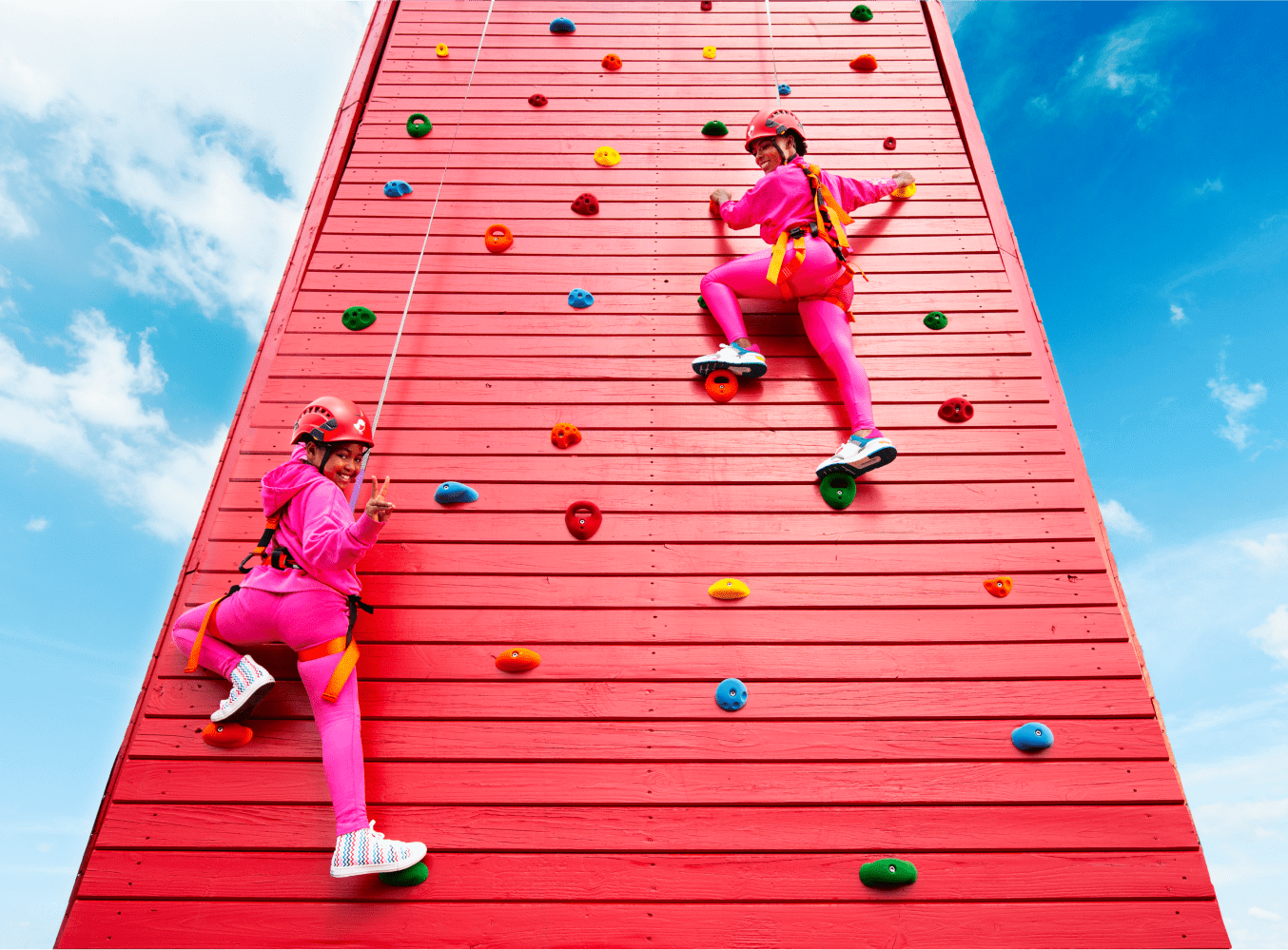 People climbing on a red climbing wall